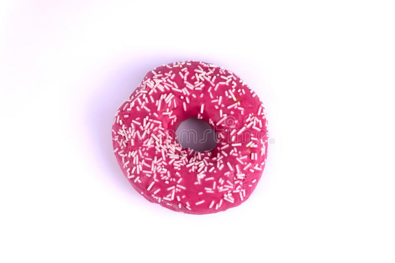 on a white background an attractive sweet donut with pink icing is decorated with white powder, a violet shade is formed from it stock photos