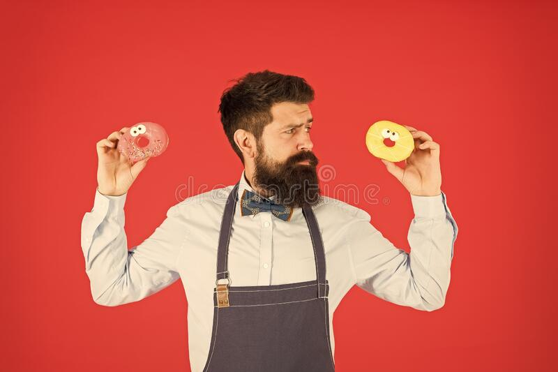 Sweet donut. Waiter in cafe. Doughnut calories. Glazed donut. Bearded well groomed man in apron selling donuts. Donut royalty free stock image