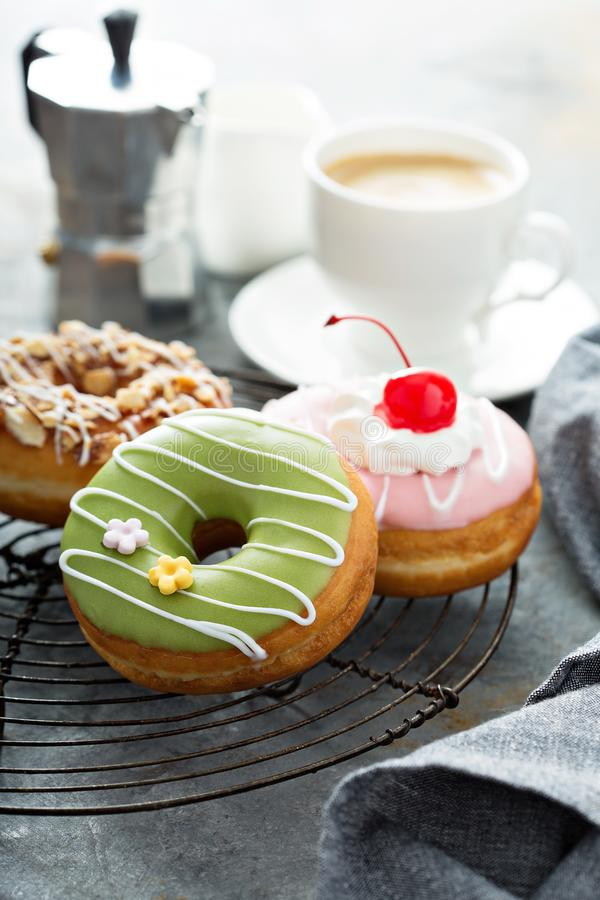 Sweet donuts on a cooling rack. Assorted glazed fried donuts with coffee for breakfast royalty free stock images