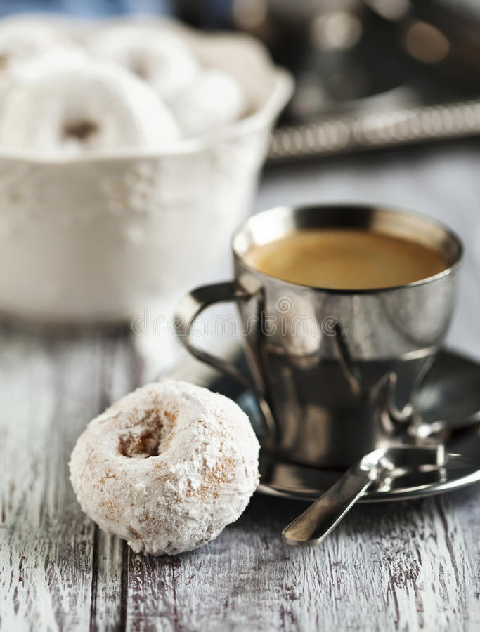 Sweet donuts with icing sugar and cup of coffee. On wooden table stock photo
