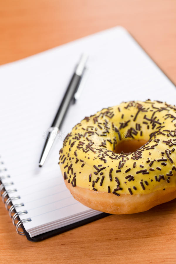 Sweet doughnut and spiral notebook stock photos