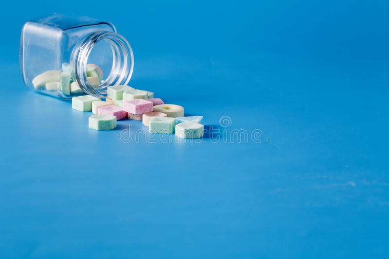 Sweet dragee spill from jar. Inviting card decoration concept. Sweet dragee spill from jar stock photos
