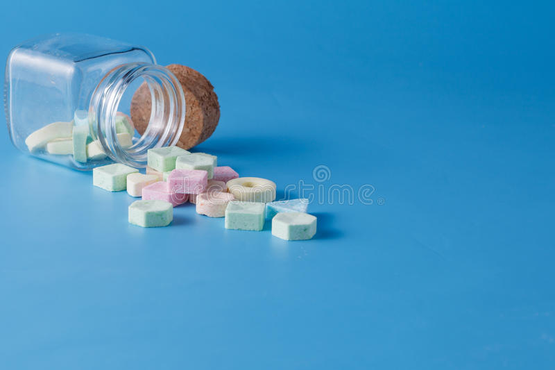 Sweet dragee spill from jar. Inviting card decoration concept. Sweet dragee spill from jar royalty free stock photo