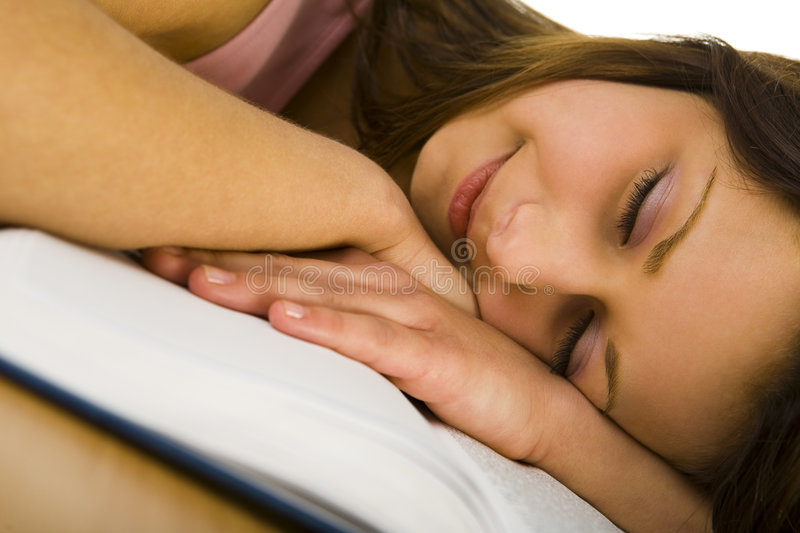 Sweet dream. Young woman sleeping with head on opened book. Closeup on face royalty free stock photo