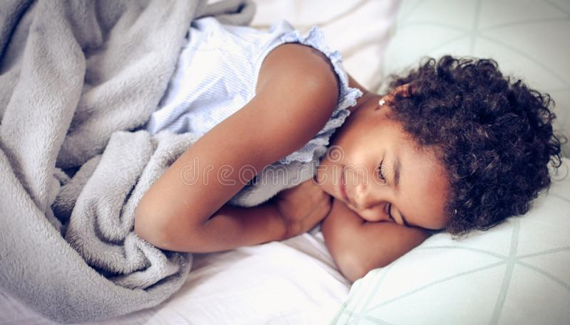 Sweet dreams. African American little girl sleeping in bed. Space for copy. Close up stock photo