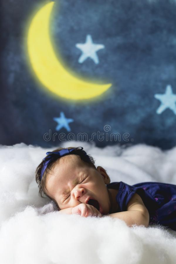 Sweet dreams. Bedtime and good night concept. Sleepy little baby. Sleepy newborn baby girl yawning on clouds with moon and stars in the background. Sweet dreams stock image