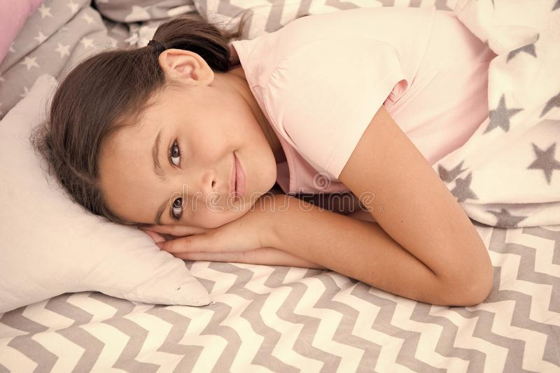 Sweet dreams. Girl smiling happy child lay on bed with star pattern pillows and cute plaid in her bedroom. Bedclothes. For children. Modern fashionable royalty free stock images