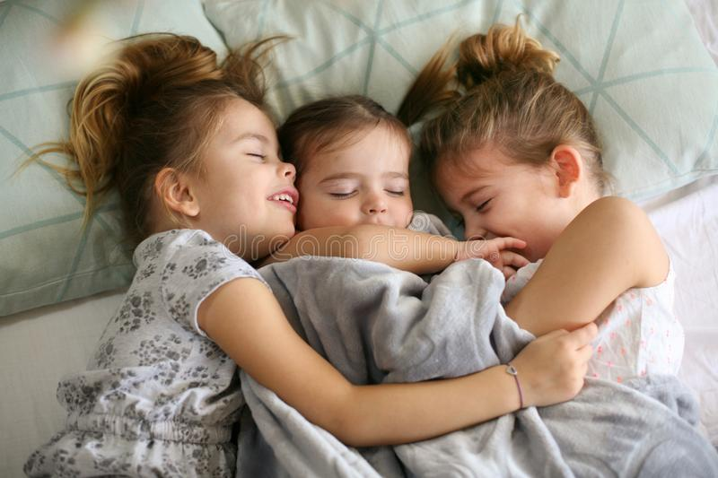 Sweet dreams. Kids on bed. Three little girls sleeping together in bed. space for copy royalty free stock photos
