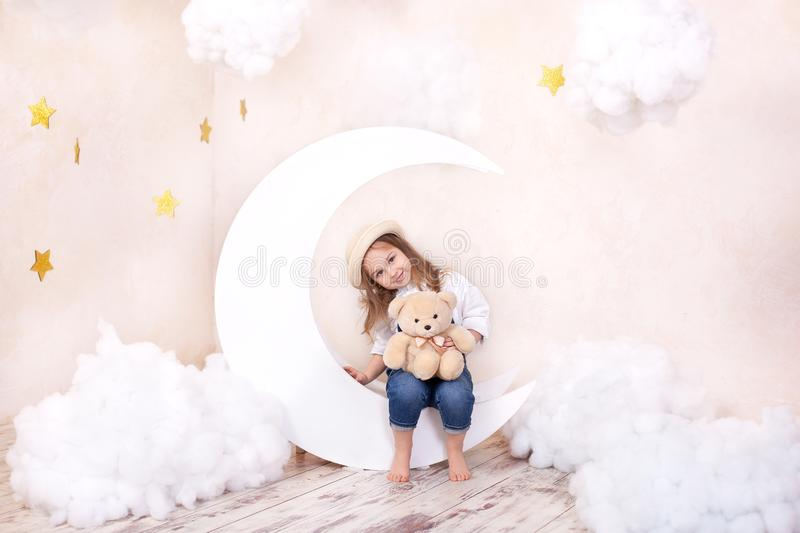 Sweet Dreams. Little cute girl sitting on the moon with clouds and stars with a teddy bear in their hands and playing. Little astr royalty free stock photo