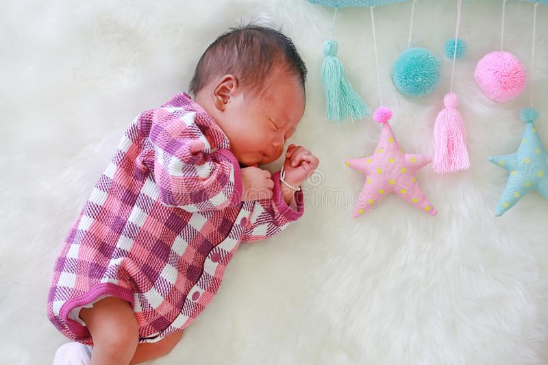 Sweet dreams newborn baby boy sleeping on white fur background with soft fabric mobile.  stock photo