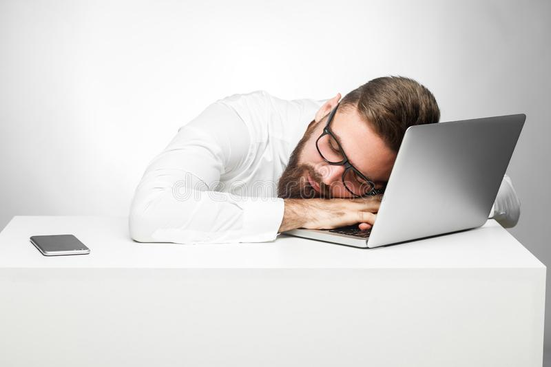 Sweet dreams in the work station. Portrait of sleepy tired freelancer in white shirt are sitting in office is snoozing at his work. Place near laptop. Indoor stock photography