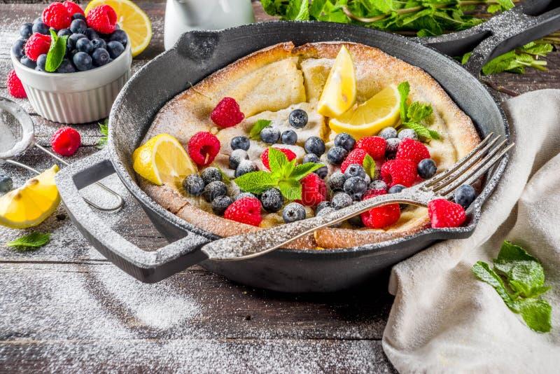 Sweet dutch baby pancake with fruit and berries. Sweet breakfast vegan dutch baby baked pancake with fruit and berries, wooden background copy space stock images