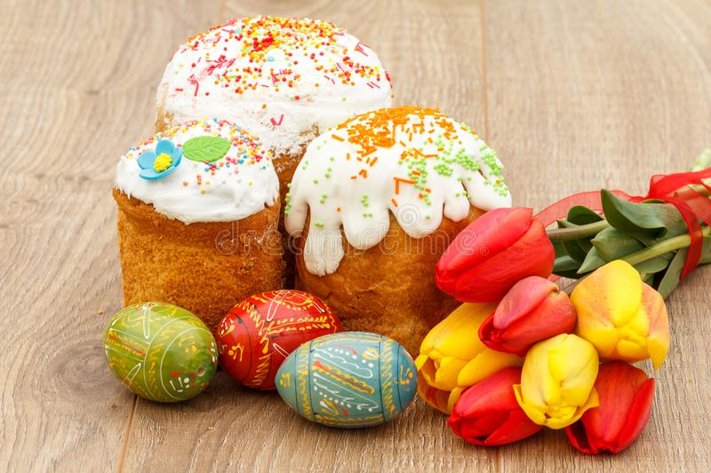 Sweet easter cakes, painted Easter eggs, red and yellow tulips o. N wooden boards royalty free stock image