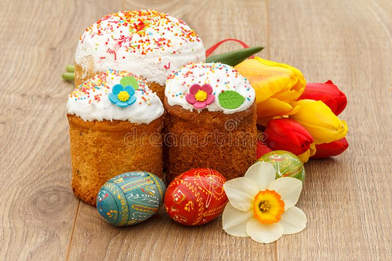 Sweet Easter cakes, painted Easter eggs, red and yellow tulips,. Narcissus on wooden boards royalty free stock images