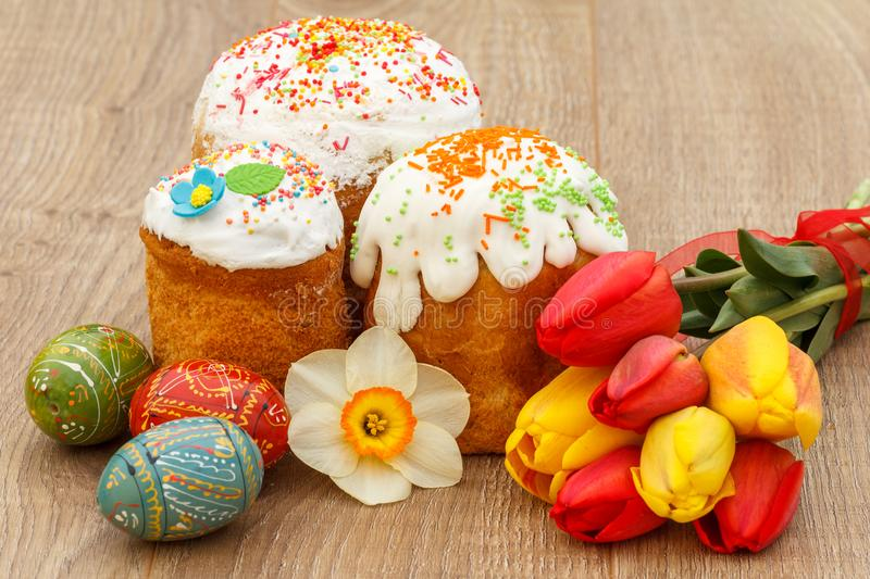 Sweet Easter cakes, painted Easter eggs, red and yellow tulips,. Narcissus on wooden boards stock photography