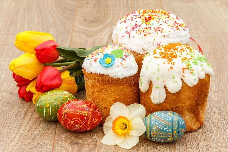 Sweet Easter cakes, painted Easter eggs, red and yellow tulips,. Narcissus on wooden boards stock photo