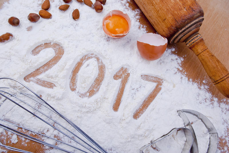 Sweet 2017. Figures 2017 written in flour on kitchen table with raw egg, nuts, whisk, casts and rolling pin, concept stock photo
