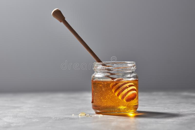Aromatic fresh organic honey with dipper in a glass pot on a gray stone table, pure natural sweet goodness. royalty free stock image
