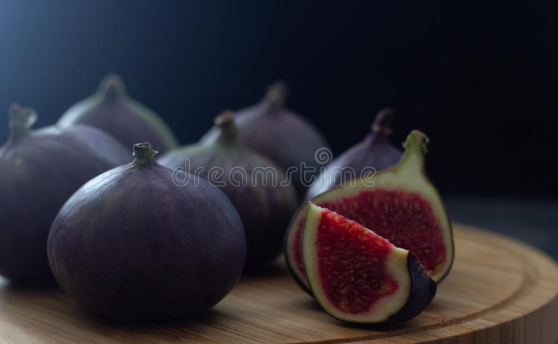 Sweet and fresh fig fruits lie on a wooden board on a dark background. Low key photo. Place for text. Sweet and fresh fig fruits lie on a wooden board on a dark stock photo