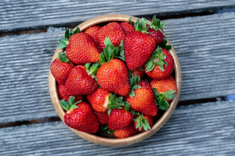 Sweet fresh juicy organic ripe strawberries in wooden bowl on wooden surface outdoors stock photo