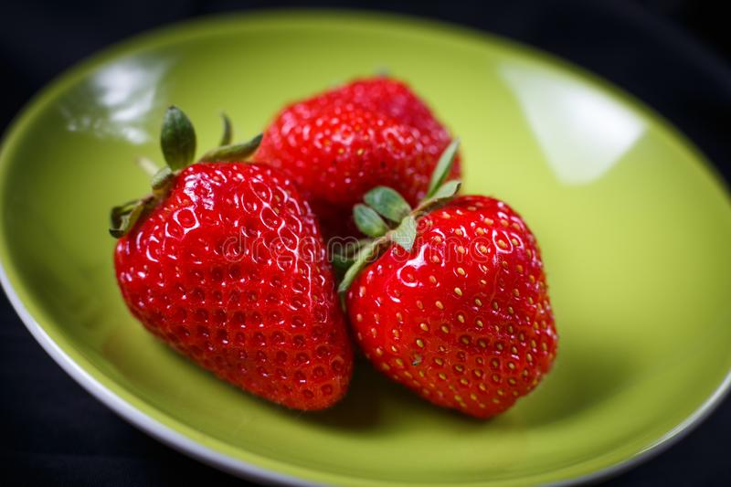 Sweet fresh strawberries on a green plate. Selective focus stock photos