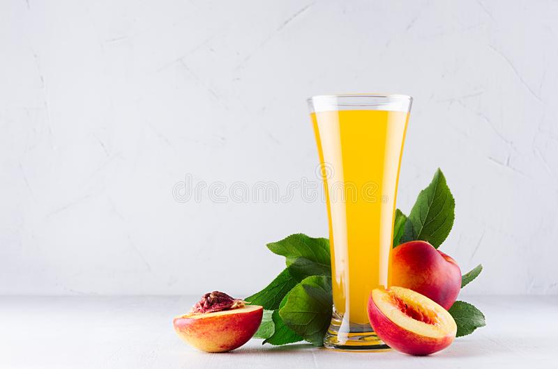 Sweet fresh yellow juice of peach and red nectarines with green leaves, juicy half cut on white wood table. stock images
