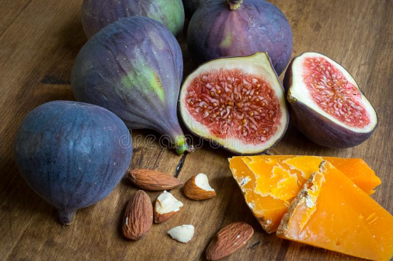 Whole and cut figs with almonds and cheese royalty free stock images