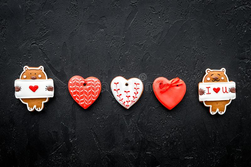 Sweet gift for St Valentine`s Day. Heart shaped gingerbread on black background top view copy space stock photo