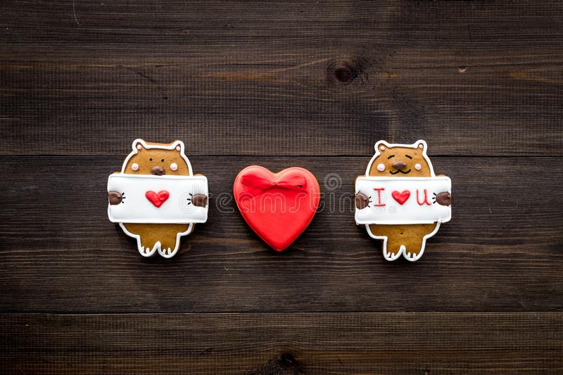 Sweet gift for St Valentine`s Day. Heart shaped gingerbread on dark wooden background top view copy space royalty free stock photo