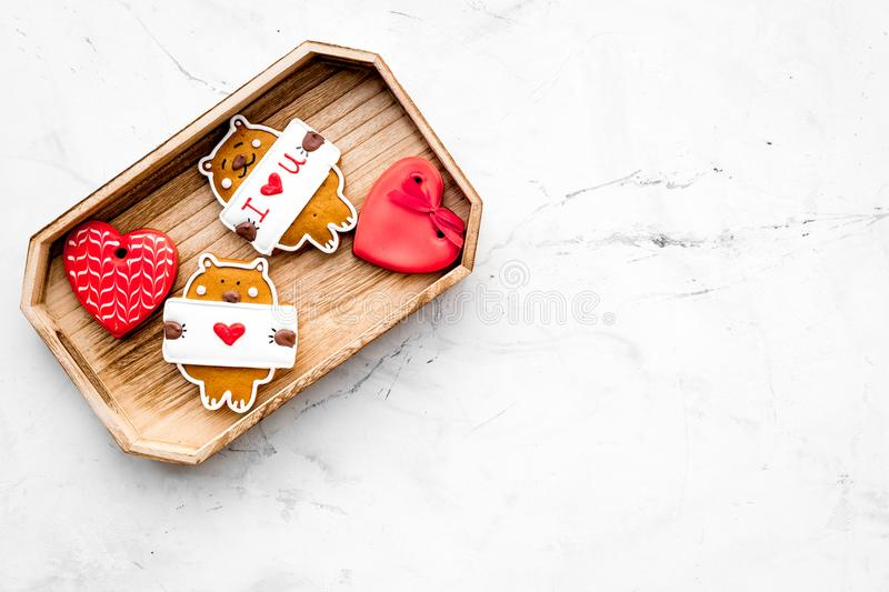 Sweet gift for St Valentine`s Day. Heart shaped gingerbread in tray on light grey background top view copy space stock photo