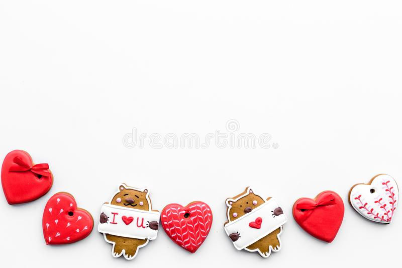 Sweet gift on Valentine`s Day. Heart shaped cookies and bear with lettering I love you on white background top view copy stock photos