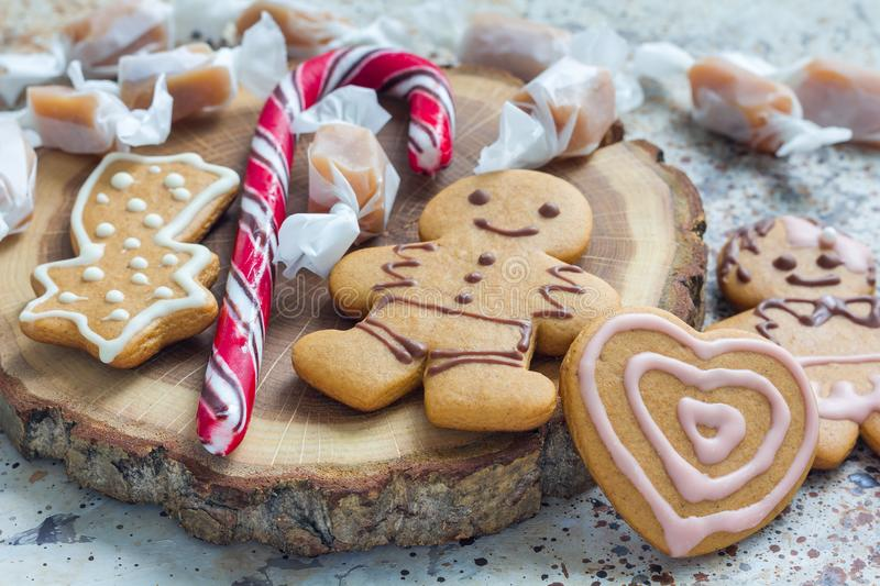 Sweet gifts for holiydays. Homemade christmas gingerbread cookies and caramel candies on wooden board, horizontal stock image