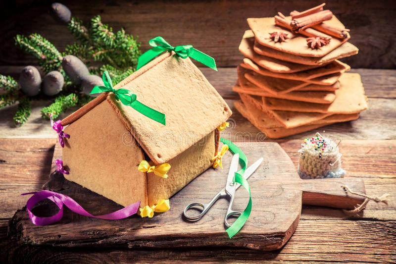 Sweet gingerbread cottage for Christmas. On old wooden table royalty free stock photography