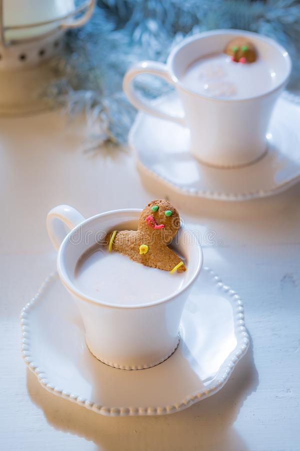 Sweet gingerbread man in hot chocolate for Christmas. On white table stock photos