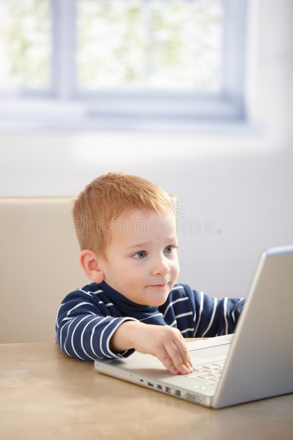 Sweet gingerish kid playing video game on laptop royalty free stock photography