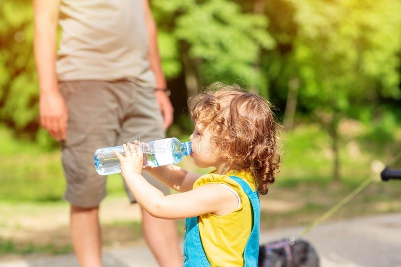 Sweet girl drinking water from the bottle outdoors. Sweet cute girl drinking water from the bottle outdoors royalty free stock images