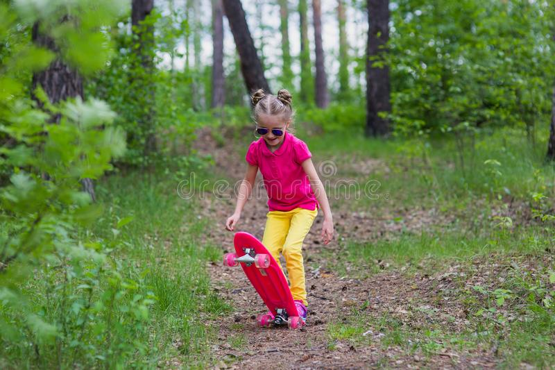 Sweet girl learns to ride a skateboard in the park stock photos