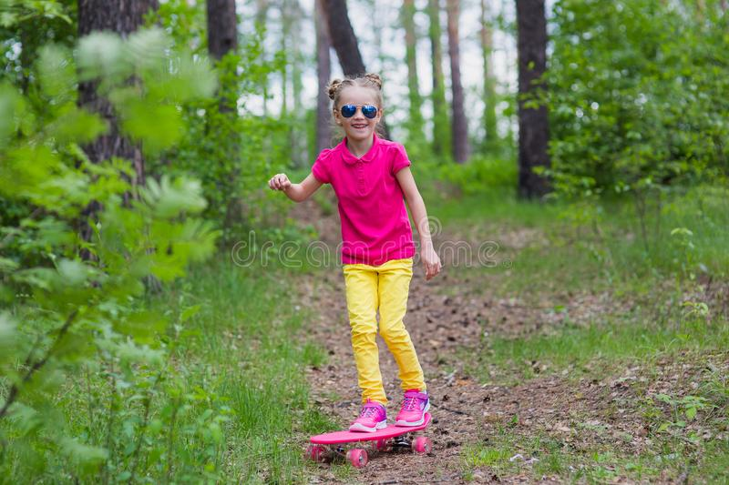 Sweet girl learns to ride a skateboard in the park royalty free stock image