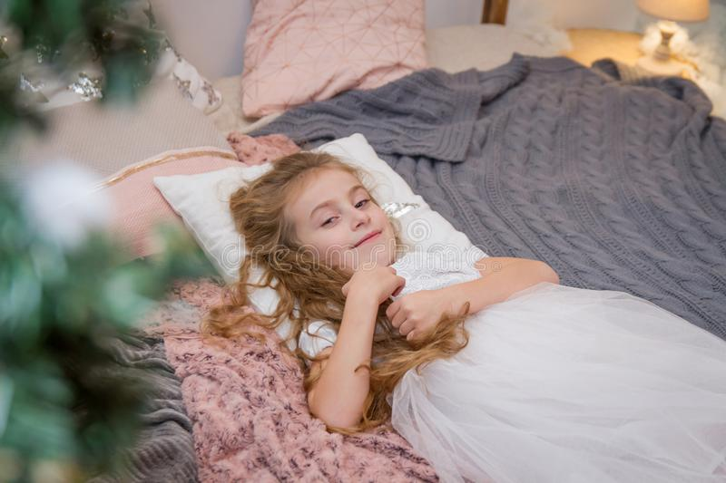 Sweet girl lying on pillow in winter studio royalty free stock images