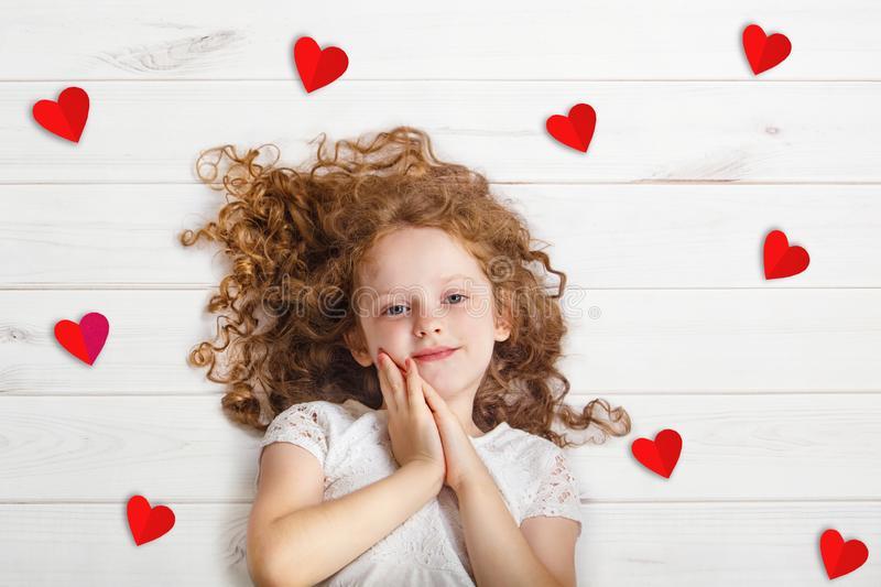 Sweet girl lying on wooden floor with red paper hearts. stock photos