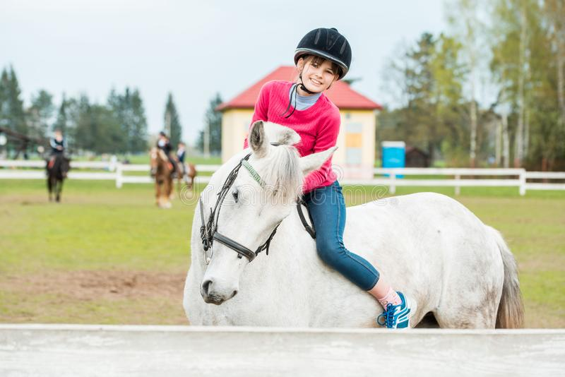 A sweet girl riding a white horse, an athlete engaged in equestrian sports, a girl hugs and kisses a horse. stock photos