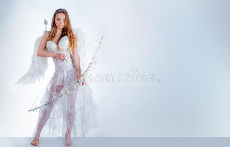 Sweet girl wearing angel costume white dress and feather wings. Happy Valentines day - copy space. Angelic character royalty free stock photo