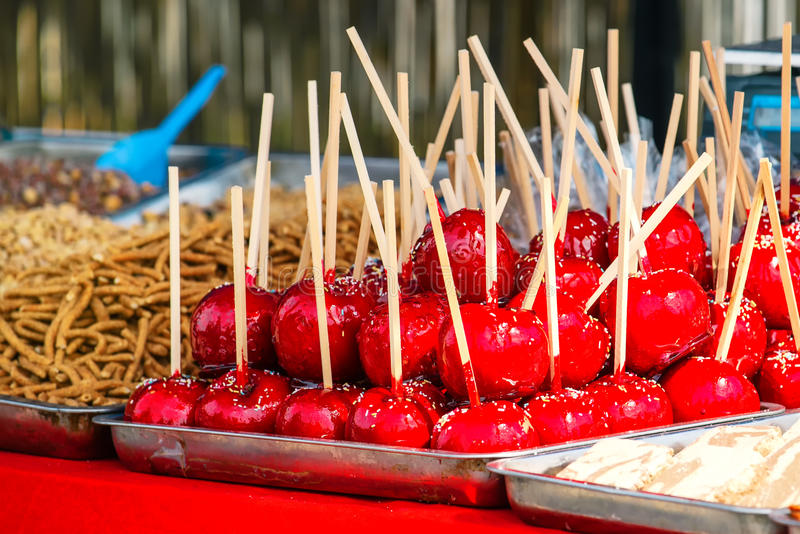 Sweet glazed red toffee candy apples on sticks. For sale on farmer market or country fair stock images