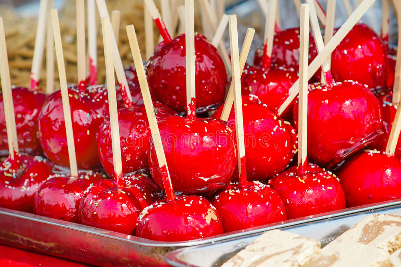 Sweet glazed red toffee candy apples on sticks. For sale on farmer market or country fair stock photo