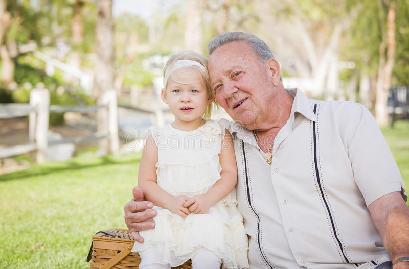 Sweet Grandfather and Granddaughter Enjoying Easter Eggs on Blanket At stock image