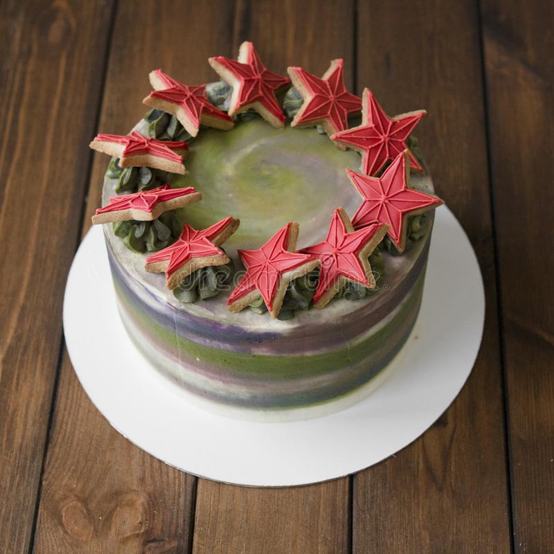 Sweet green-gray cake with decor on 23 february holiday - Red stars cookies and number 23 - on wooden background. Close royalty free stock images