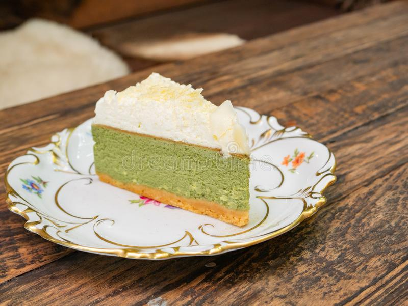 Sweet green tea cheesecake topping with white chocolate put on a white plate. That placed on solid wood table stock image