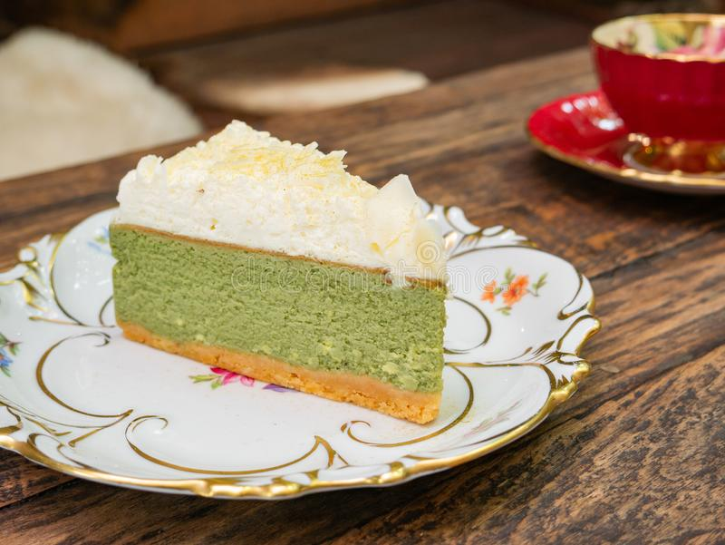 Sweet green tea cheesecake topping with white chocolate put on a white plate. That placed on solid wood table with a red teacup for background royalty free stock image
