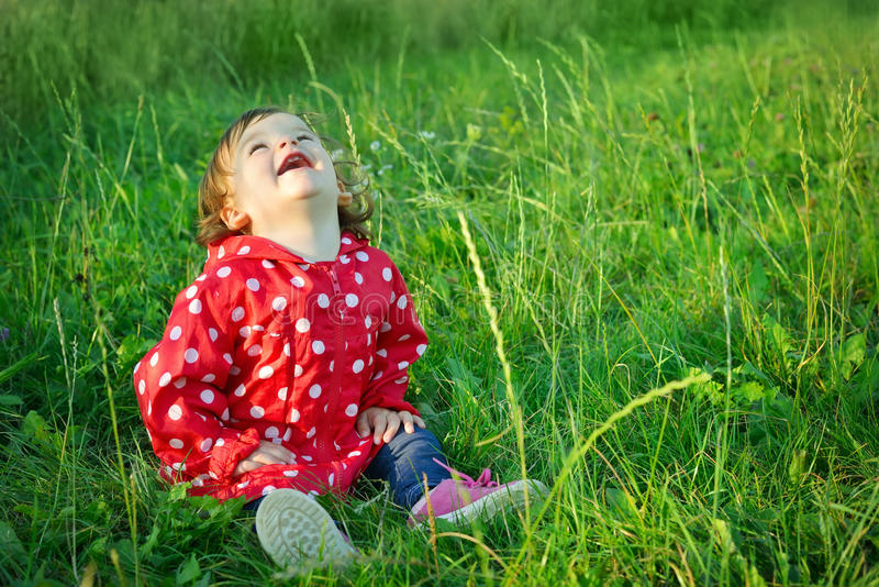 Sweet happy little girl sitting in grass outdoor. Cute baby with curly hair laughting. Young girl posing in park. Smiling kid. royalty free stock photos