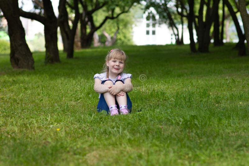 Sweet, happy little girl sitting on a grass in a park royalty free stock images